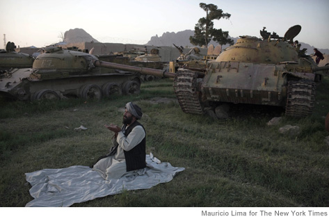 A former Afghan Mujahedeen fighter performs a sunset prayer near Soviet tanks destroyed during the 80's in Kandahar, Afghanistan, on May 9, 2011. Kandahar, the biggest city in southern Afghanistan and a major base for NATO forces, continues to be a target for the Taliban who opened their spring offensive with an attack on the area. (Mauricio Lima/The New York Times)